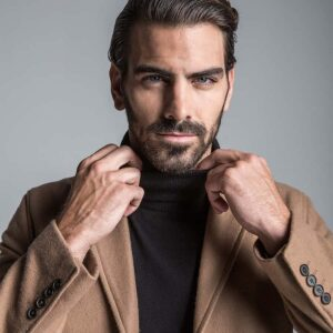 Image of model Nyle DiMarco, wearing a black turtle neck and brown, collared coat.